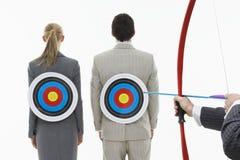 Abzielen des Pfeiles auf Ziele auf den Rückseiten der Geschäftsleute Lizenzfreie Stockfotografie