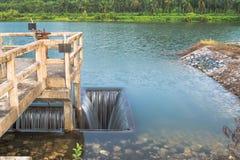 Abzugsgrabeneinlaß von Wehrwassertor-Infrastrukturüberlauf vom See Lizenzfreies Stockbild
