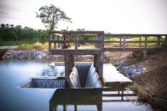 Abzugsgrabeneinlaß von Wehrwassertor-Infrastrukturüberlauf vom See Lizenzfreies Stockfoto