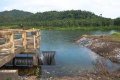 Abzugsgrabeneinlaß von Wehrwassertor-Infrastrukturüberlauf vom See Lizenzfreie Stockbilder