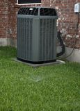 AC on backyard. Air conditioner and sprinkler on brick wall background Royalty Free Stock Photography
