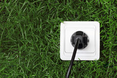 AC outlet on a green grass background Royalty Free Stock Photo