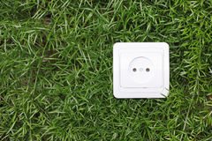 AC outlet on a green grass background Royalty Free Stock Image