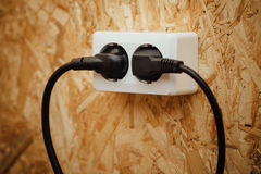 AC power plug and socket, wooden wall background Stock Photography