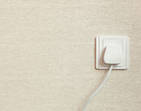 AC power plug in wall socket Stock Photos