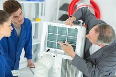 3 ac technici die industriële airconditioningscompressor herstellen stock fotografie