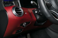 AC Ventilation Deck in Luxury modern Car Interior. Modern car interior details with red and black leather with red stitching. Carbon panel. Perforated leather royalty free stock images