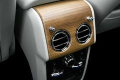 AC Ventilation Deck in Luxury modern car Interior. Modern car white leather interior. with stitching. Natural wood. Perforated lea. Ther. Car detailing. Car royalty free stock images