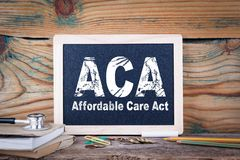 Aca, affordable care act. Chalkboard on a wooden background.  royalty free stock photography
