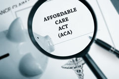 Aca search. Magnifying glass over Affordable Care Act policy and piggy bank Stock Photos