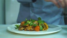 Acabamiento del cocinero y verduras comida del adorno que él se preparó, un plato con la carne de cerdo y almacen de video