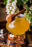 Acacia honey in gar on wooden background. Spring mood. Selective focus. Toned image. Sweet honey in jars and acacia flowers  on white Stock Images