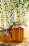 Acacia honey jarson wooden carved board. Acacia branches with flowers drooping down and touching covers, vertical royalty free stock photos