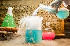 Academic chemical lab with color beakers in school. On old wooden table Stock Images