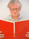 Academic, der ein rotes Buch liest. Lizenzfreies Stockfoto