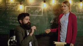 Academic man and woman writing math formulas on blackboard and discussing ideas. Teacher in classroom. Teacher and stock footage