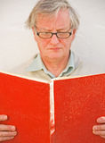 Academic reading a red book. Royalty Free Stock Photo