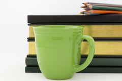 Academic work and study. Green mug in front of books with colored pencils on top reflect alert attention to academic study and intellectual work Royalty Free Stock Photo