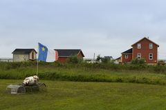 Acadian flag on pole with lobster cages in field and clapboard houses on Magdalen Islands. Ragged Acadian flag on pole with lobster cages in field and clapboard Stock Image