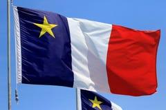 Acadian flagga med bakgrund för blå himmel Arkivbild