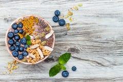Acai早餐superfoods圆滑的人滚保龄球冠上与chia、胡麻和南瓜籽、蜂花粉、格兰诺拉麦片、椰子和蓝莓 库存照片