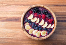 Acai berry smoothie in a wooden bowl topped with bananas, blueberries, raspberries and blackberries. Healthy,acai berry smoothie in a wooden bowl topped with Royalty Free Stock Photos