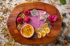Acai bowl smoothie with passion fruit and raspberries. Acai bowl smoothie with passion fruit maracuya seeds banana and raspberries Stock Image