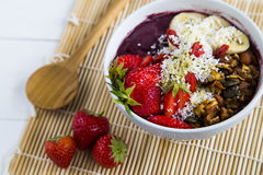 Acai bowl and strawberries. Bowl of acai purée with toppings of banana, strawberry, granola and seeds Royalty Free Stock Photos