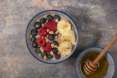 Acai bowl topped with fruit and granola with honey stock image