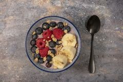 Acai bowl topped with fruit and granola on a rustic background royalty free stock image