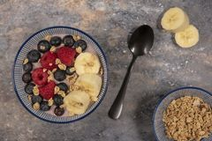 Acai bowl topped with fruit and granola on a rustic background stock photo