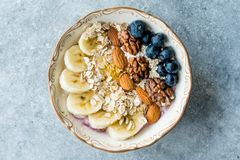 Acai Bowl with Yogurt, Blackberry, Banana Slices, Walnut, Honey, Jam, Oat, Almond, Sesame Seeds and Granola in Porcelain Bowl stock photos