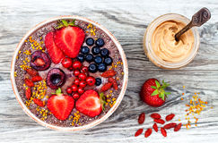 Acai breakfast superfoods smoothies bowl with chia seeds, bee pollen, goji berry toppings and peanut butter. Overhead Stock Photos