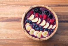 Acai jagodowy smoothie w drewnianym pucharze nakrywającym z bananami, czarnymi jagodami, malinkami i czernicami, Zdjęcia Royalty Free