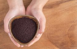 Acai powder in bowl between hands - Euterpe oleracea Stock Image