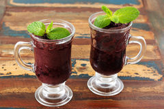 Acai pulp in 2 glass with fresh mint on wooden table. Selective focus Royalty Free Stock Photography