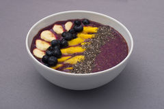 Acai smoothie bowl topped with chia seeds, mango slices, blueberries and bananas Royalty Free Stock Photo