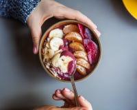 Acai smoothie, granola, frö, nya frukter i en träbunke i kvinnliga händer på den gråa tabellen Äta den sunda frukostbunken överka arkivfoton