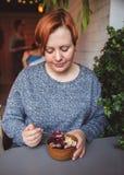 Acai smoothie, granola, frö, nya frukter i en träbunke i kvinnliga händer på den gråa tabellen Äta den sunda frukostbunken arkivbilder
