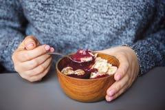 Acai-Smoothie, Granola, Samen, frische Früchte in einer hölzernen Schüssel in den weiblichen Händen auf grauer Tabelle Essen der  stockbild