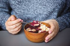 Acai smoothie, granola, seeds, fresh fruits in a wooden bowl in female hands on grey table. Eating healthy breakfast bowl stock image