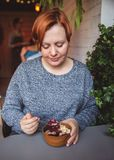 Acai smoothie, granola, ziarna, świeże owoc w drewnianym pucharze w żeńskich rękach na popielatym stole Jeść zdrowego śniadaniowe obrazy stock