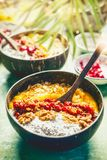 Acai smoothie mango bowls with chia seeds yogurt pudding and cranberries, nuts, oatmeal topping in coconut shells with spoon, top. View. Healthy clean breakfast stock photos
