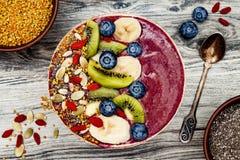 Acai superfoods śniadaniowi smoothies rzucają kulą z chia ziarnami, pszczoły pollen, goji jagodowymi polewami i owoc, overhead Od zdjęcie stock