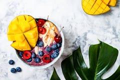 Acai superfoods smoothie śniadaniowy puchar z mango, czarna jagoda, wiśnia, kokosowi płatki Koszt stały, odgórny widok Fotografia Stock