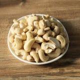 Acajounüsse auf einem hölzernen Hintergrund in einer Platte Schöne Nüsse auf dem Tisch lizenzfreie stockfotografie