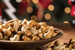 Acajounüsse in einer Schüssel auf dem Brett mit unscharfem Weihnachtshintergrund Stockbild