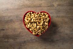 Acajounüsse im Herztopf auf hölzernem Hintergrund Lizenzfreie Stockfotografie