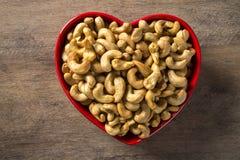 Acajounüsse im Herztopf auf hölzernem Hintergrund Stockfoto