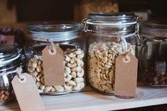Acajounüsse und Erdnüsse in den Glasgefäßen Stockfoto